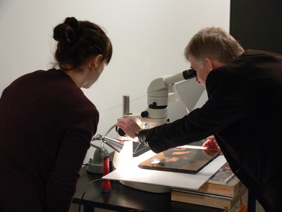 Ron Spronk (and Brandi MacDonald) examining the Adrien Brouwer painting with a microscope.